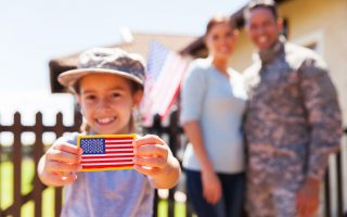 50864636 - little girl holding american flag badge in front of parents